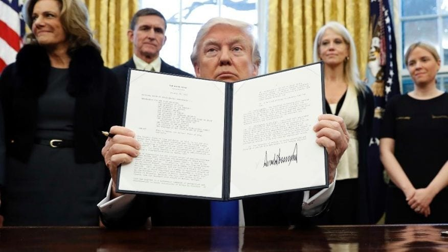 Seated in the White House and surrounded by smiling aides and advisers, President Trump holds up a signed executive order.