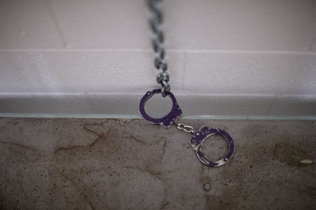 A picture of locked handcuffs attached by chains to a white stone wall.
