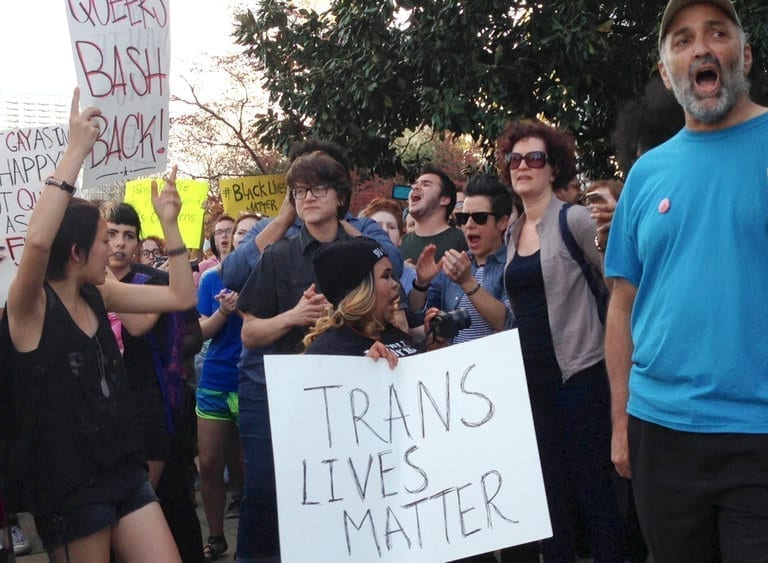 A protester holds a sign reading Trans Lives Matter