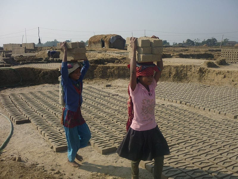 Two Nepalese girls carry bricks atop their heads.