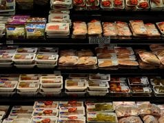 A selection of packaged, processed meat products in a grocer's refrigerated meat case.