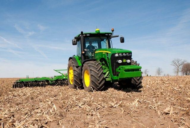 A John Deere 8320R tractor sits in a field of crop stubble, under a blue sky.