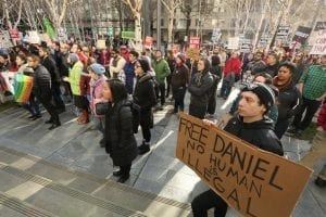 """A young man carrying a sign reading """"Free Daniel - No Human is Illegal"""" stands in front of a crowd of supporters gathered outside a Seattle courthouse in protest of immigrant Daniel Medina Ramirez's detention."""