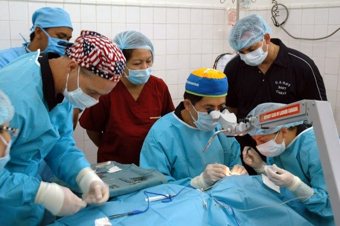 A group of doctors operates on a patient in a hospital setting.