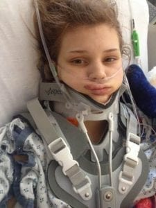 Makenzie Wethington in a hospital bed with numerous tubes inserted into her nose and mouth; she also has a large brace covering the visible portion of her upper body.