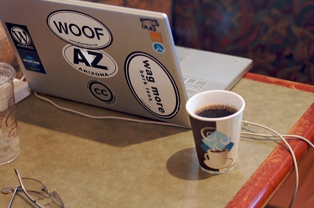 A sticker-covered laptop computer and a mug of coffee sit on a coffeehouse table.