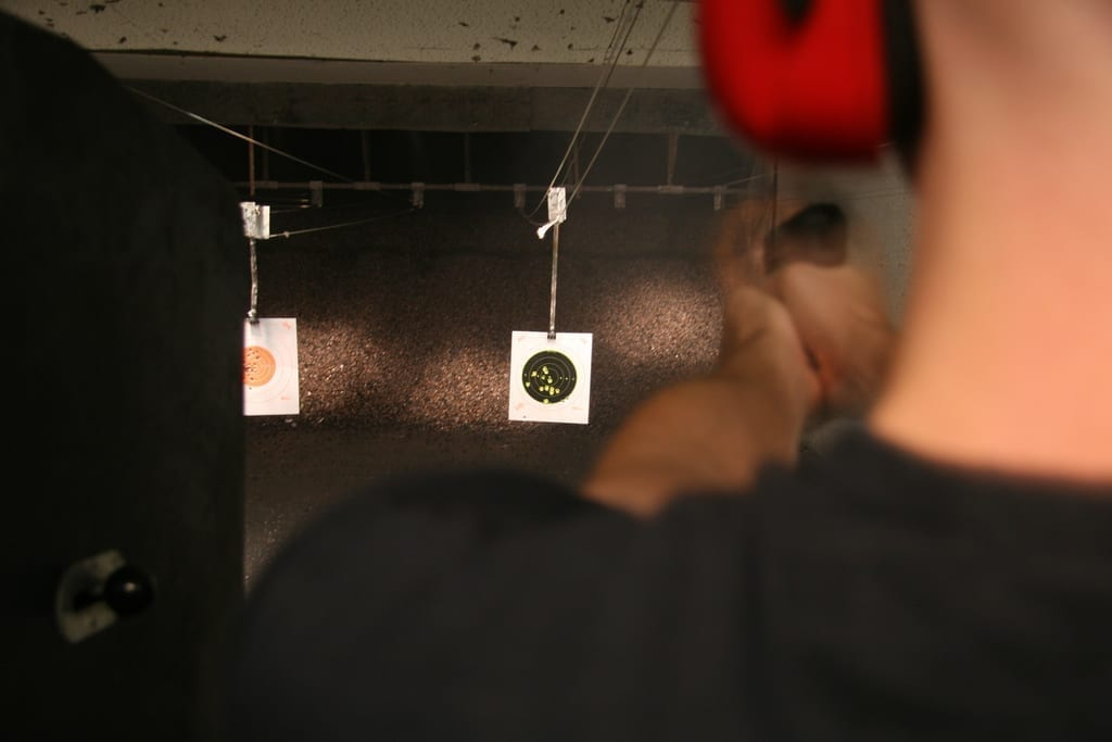 A black-clad man fires a gun at a target at a shooting range. We observe the target from over his left shoulder.