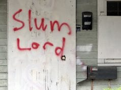 """The words """"Slum Lord"""" are scrawled in red paint on the front door of a dwelling."""