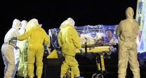 Medical workers donning yellow hazmat suits assist a man contained within a quarantine tube.