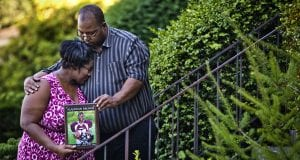 Ayanna Brown, overcome by grief, holds a picture of her son while crying into the shoulder of her husband Louis