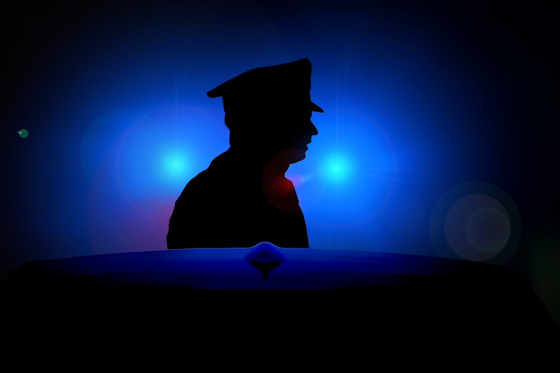 Police officer in silhouette with blue lights in background; image by geralt, via Pixabay, CC.0.