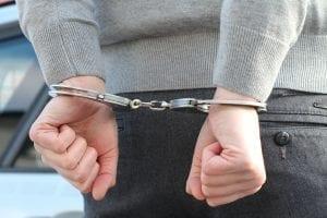 Man in handcuffs; image via Pxhere, CC0.