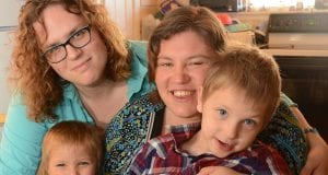 Tonya and Rachel Smith pictured smiling with two young children.