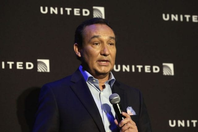 Oscar Munoz holds a microphone and speaks at a press conference