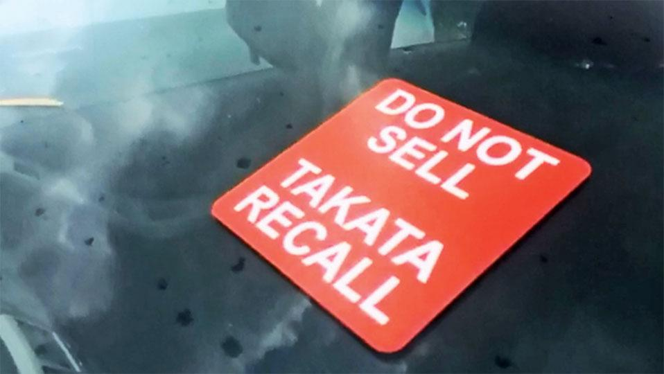 Vehicle windshield with sign saying Do not sell, Takata recall.