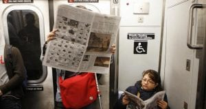 A man wearing a leg brace and stands alongside a pair of crutches while a woman sits in a handicap-designated seat on the New York City subway.