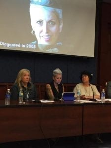 "Heather seated at a table with two other women; a slide show or movie in the background has Heather's face superimposed on a screen with the words ""Diagnosed in 2005"" reading across the bottom."