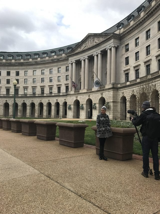 Heather Von St. James stands outside the EPA building in Washington, D.C., with a photographer in the foreground.