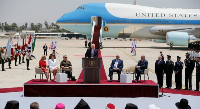 Donald Trump speaking at a podium with Israeli officials in the foreground and a glimmering Air Force One behind.