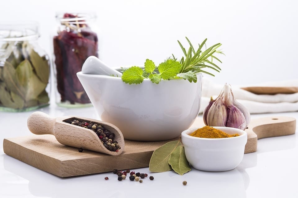 An array of herbs and spices, including peppercorns and garlic, surround a cutting board and a mortar and pestle.