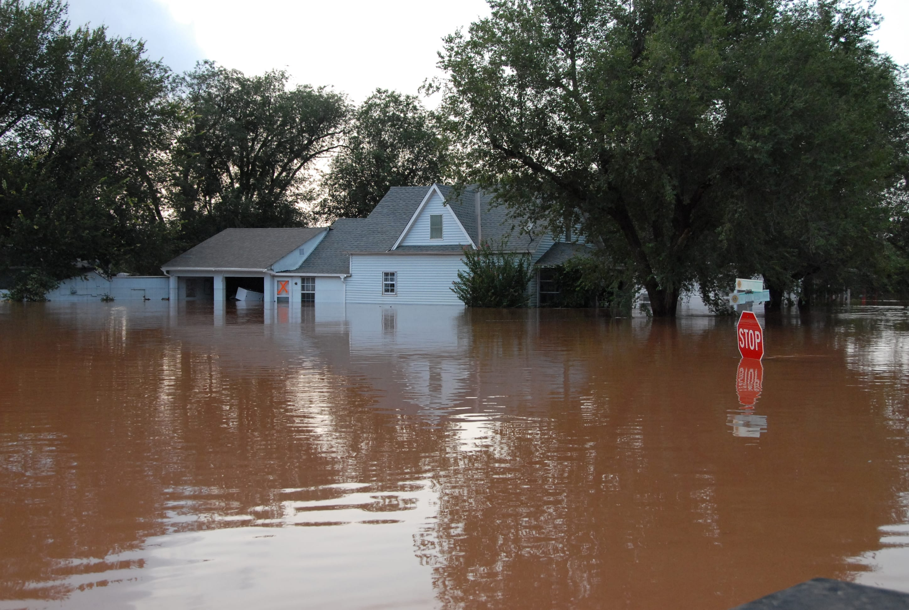 A flooded street in Kingfisher, Oklahoma, with water engulfing a house and standing nearly as high as a stop sign.