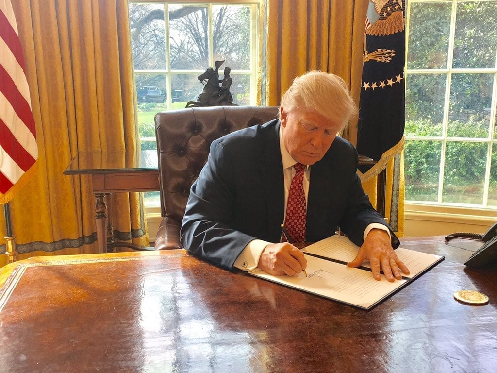 Trump signing document; image by Sean Spicer, White House Press Secretary, Public domain, via Wikimedia Commons.