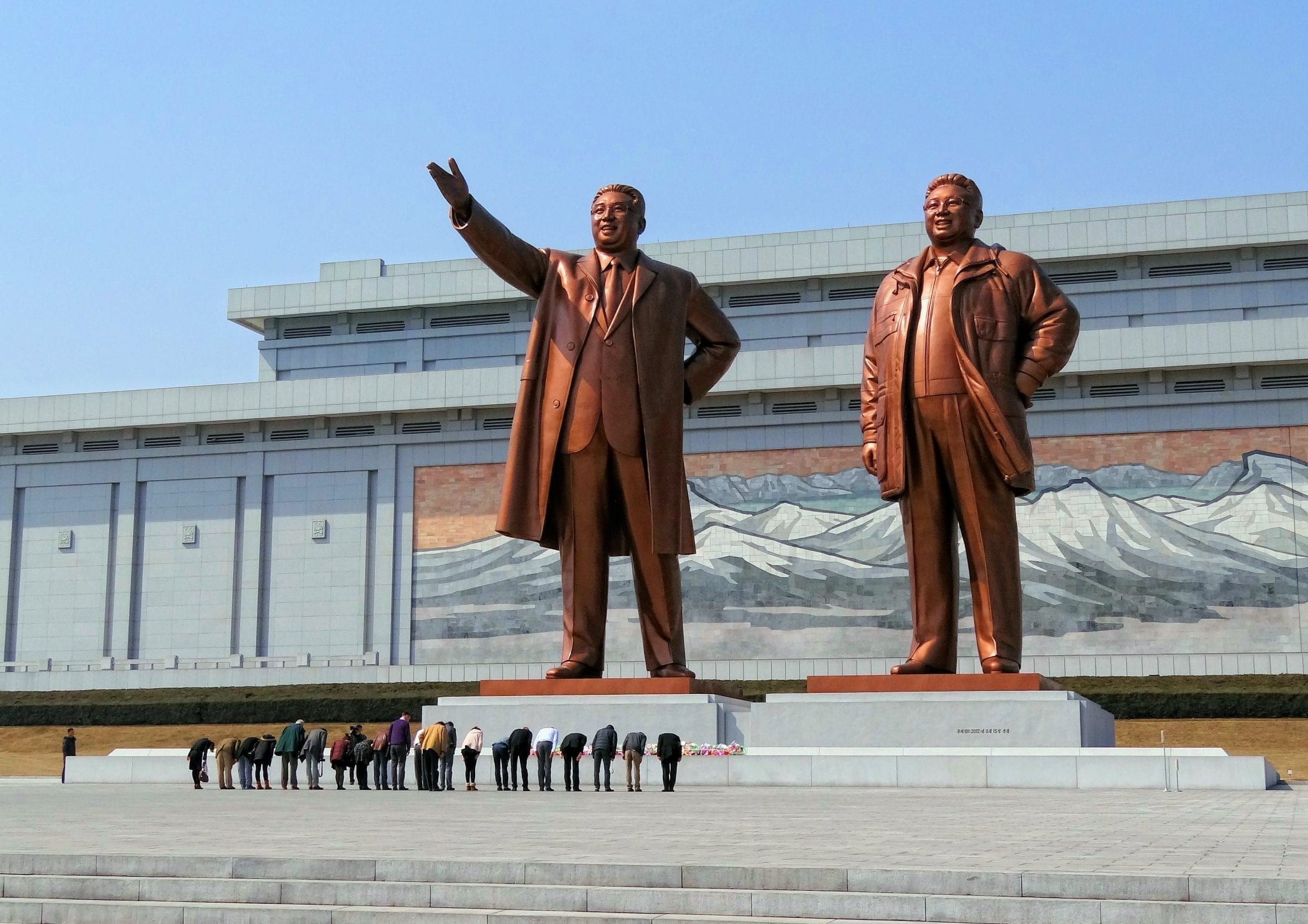Visitors bowing in a show of respect for North Korean leaders Kim Il-sung and Kim Jong-il on Mansudae (Mansu Hill) in Pyongyang, North Korea; image by Bjørn Christian Tørrissen (Own work), CC BY-SA 3.0, via Wikimedia Commons, no changes.