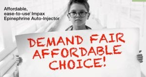 """Boy holding a sign saying """"Demand fair affordable choice"""" referring to epinephrine autoinjector prices."""
