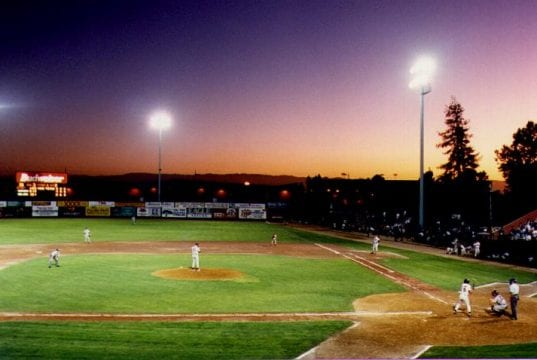 Baseball field illuminated by lights at night.