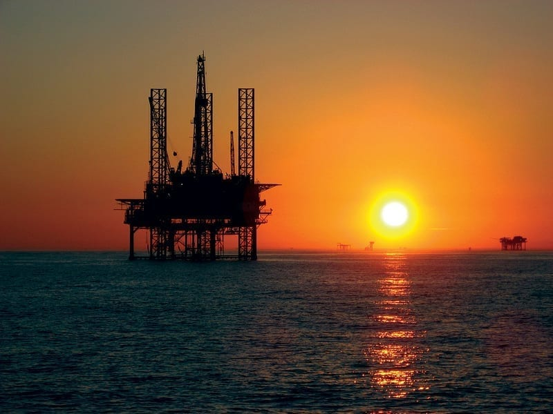 An offshore drilling rig stands in silhouette against a setting sun.
