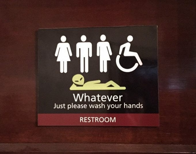 A bathroom door sign showing figures of a woman, a man, a gender-nonspecific individual, a handicapped wheelchair, and an alien. It says, Whatever. Just wash your hands.