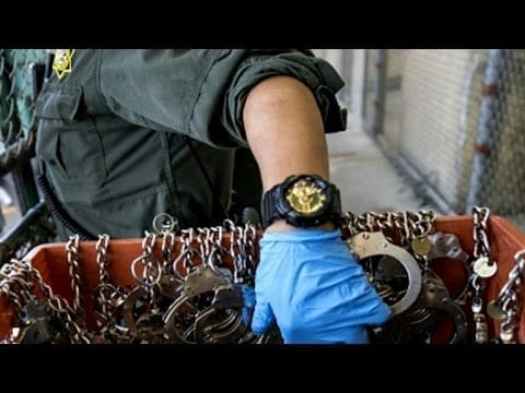 A police officer wearing a blue glove reaches into a bin of handcuffs and restraints.