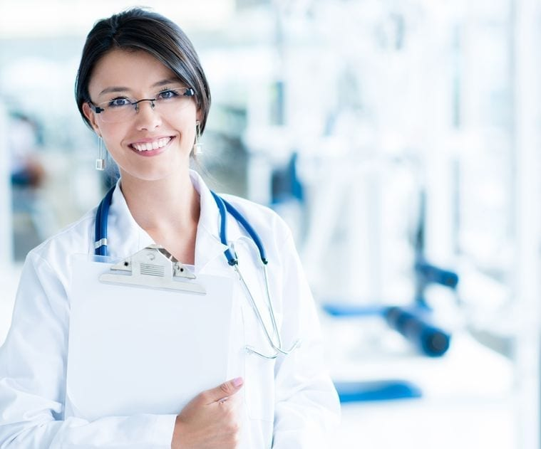 A smiling, dark-haired female doctor holds a clipboard.