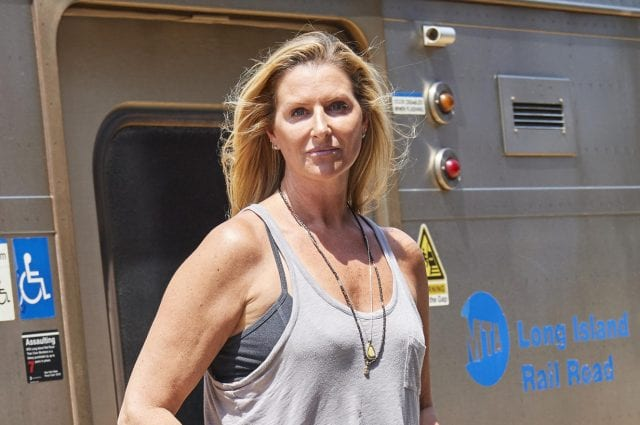 A glowing Meredith Jacobs poses for a glamour shot in front of an LIRR carriage.