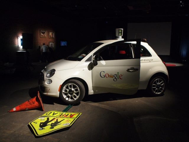 A Google driverless car is pictured in shadows, having run over a cone and a safety sign.
