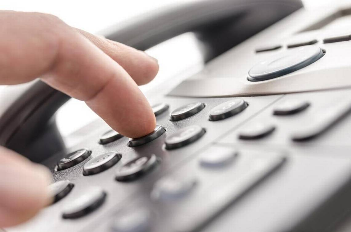 Stock image of telephone and fingers pressing buttons