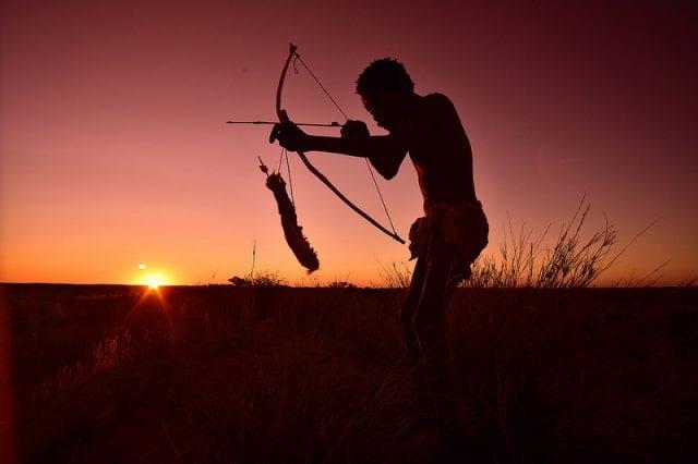 A Kalahari Bushman with bow and arrow, at sunset.