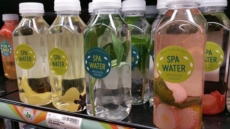 Bottles of water with small chunks of fruit for flavoring sit on a shelf at Whole Foods Market.