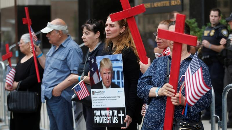 Protesters hold signs decrying the scheduled deportation of Iraqi nationals.