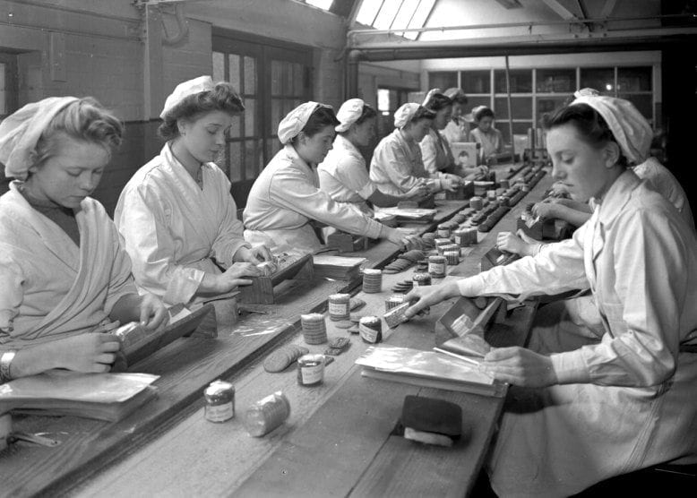 Women in white coats and hair coverings produce biscuits in a factory.