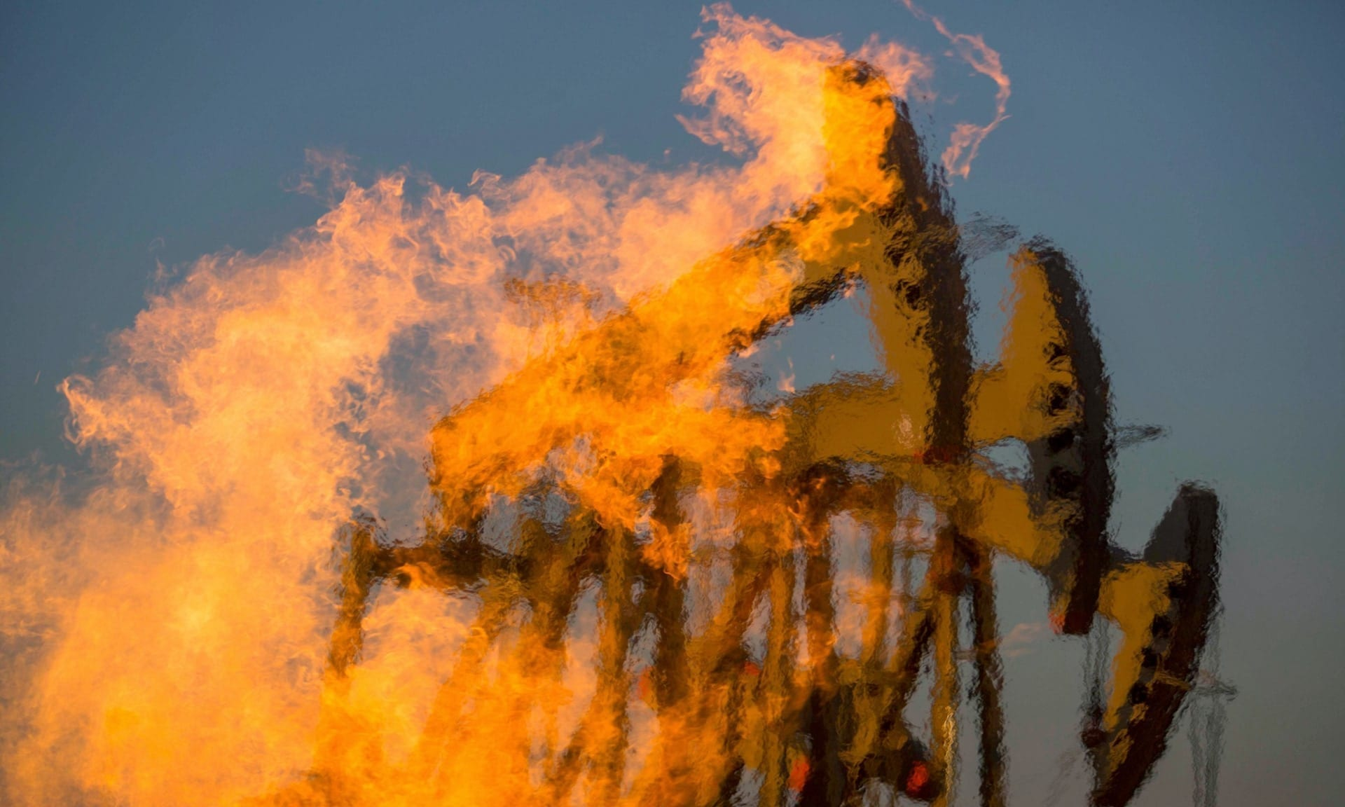 Flames in the foreground of a photo showing fracking facility