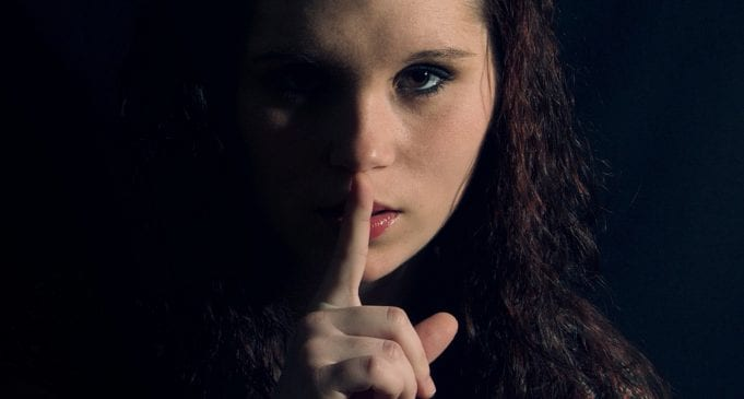 A woman holds her finger to her lips in the classic Shhhh position.