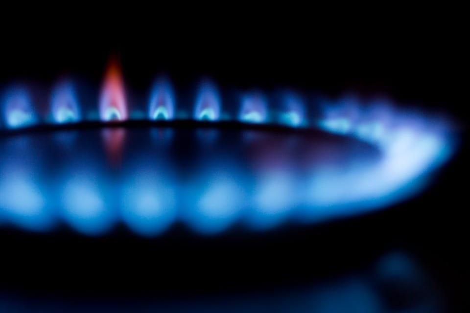 Blue flames from a natural gas burner form a ring in the dark.