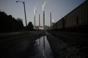 Smokestacks emit gas into the atmosphere, with a polluted body of water in the foreground.