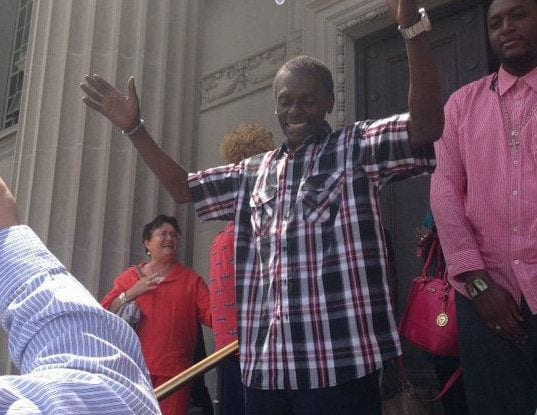 Reginald Adams lifting arms to the sky as he celebrates his exoneration.