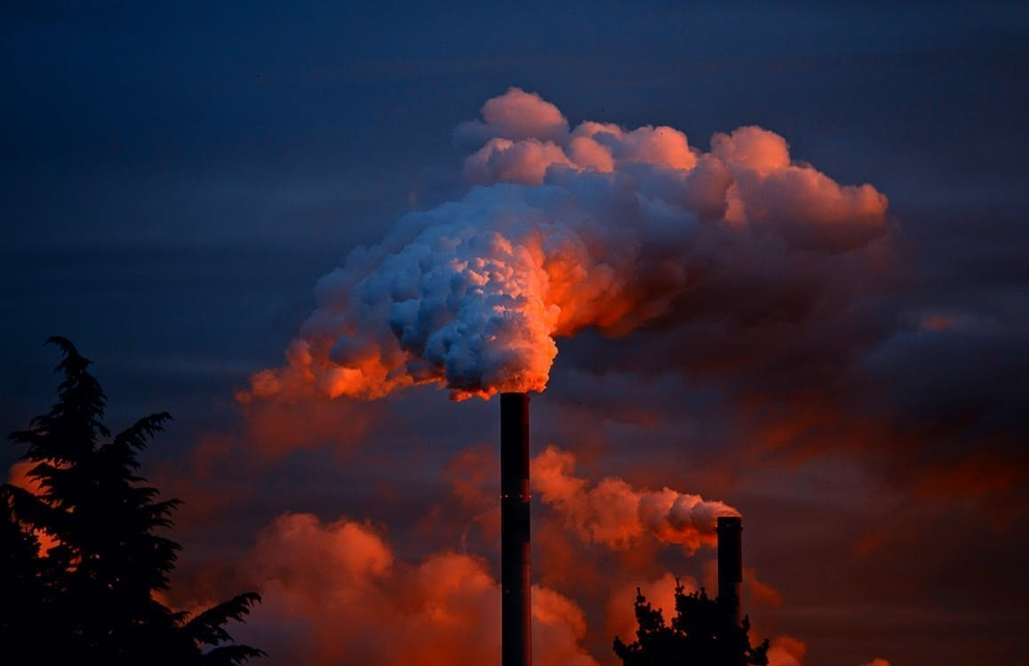 A smokestack emits pollution into a stark, ominous sky.