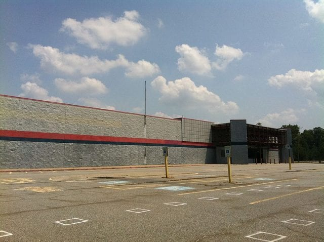 An abandoned Walmart, what's known as a dark store, falls apart in an empty parking lot.