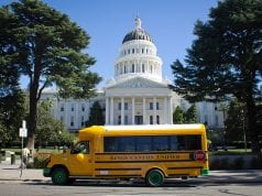 An electric school bus sits parked in front of California's capitol building.
