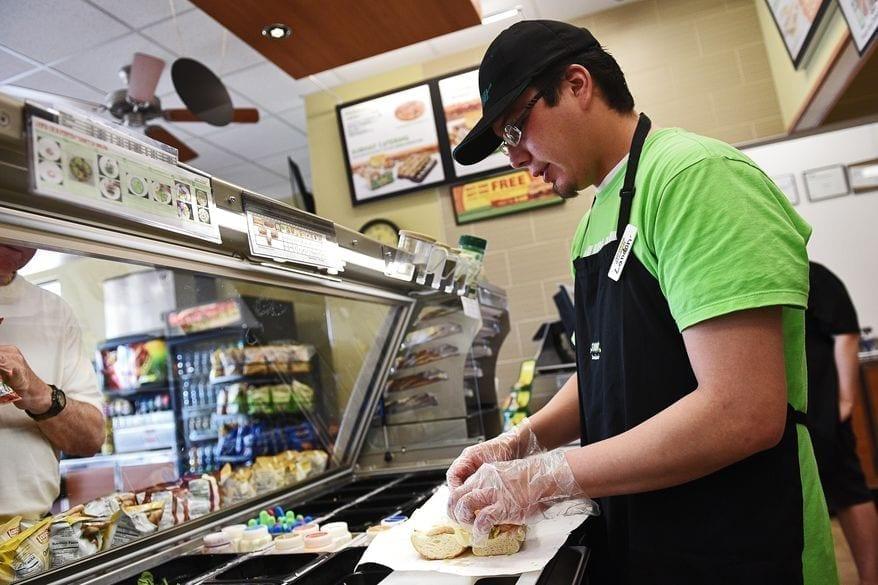 Image of a Subway Employee Making Sandwich