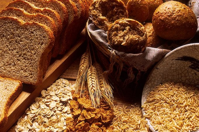 A sliced loaf of brown bread, a basket of rolls and 4 types of grains sit on a wooden table.